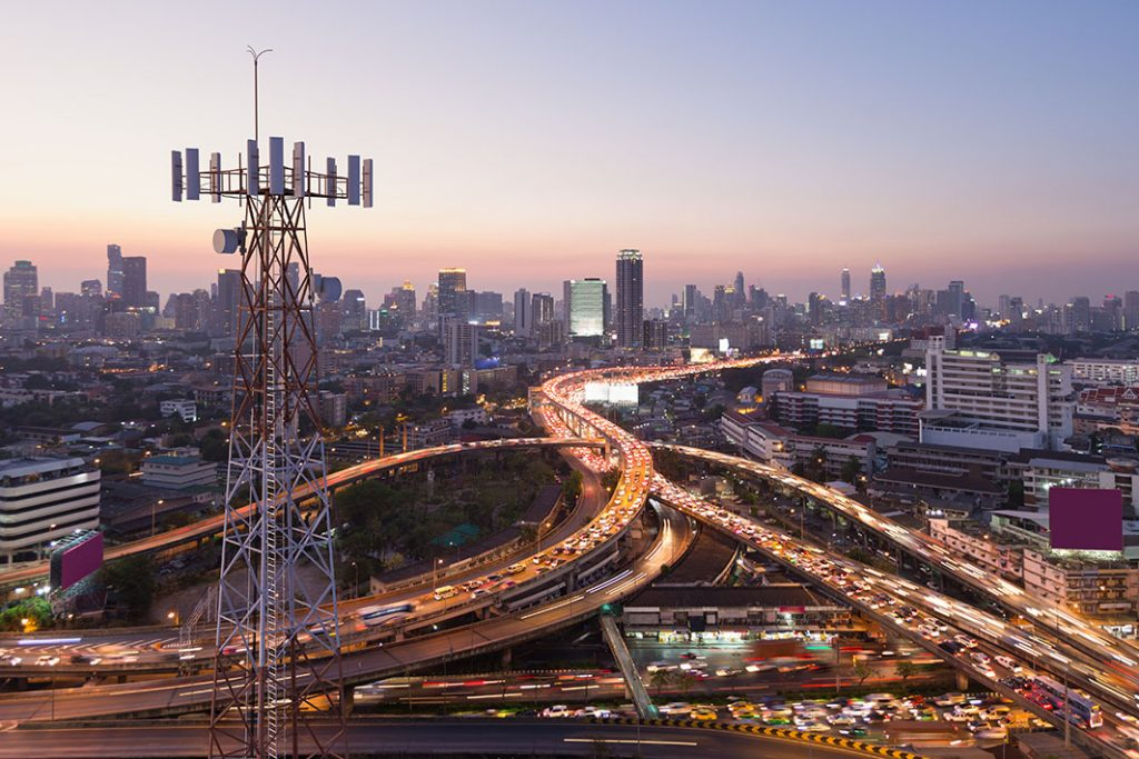 Telecommunication tower with 5G cellular network antenna on city